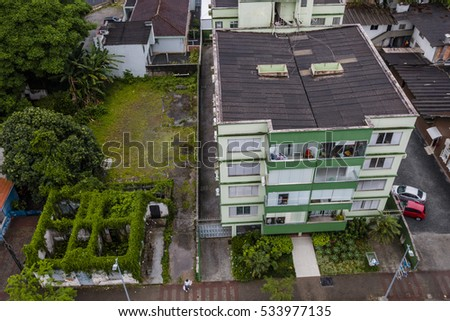 JOINVILLE, BRAZIL - DECEMBER 2016: Ruin with vegetation next to residential building