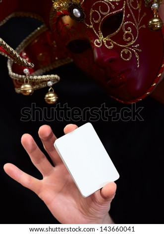 joker in in mask with white card - stock photo