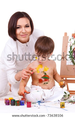 Joking happy smiling mother in white painting her son's hands