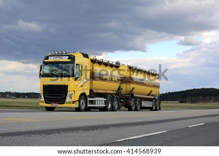 JOKIOINEN, FINLAND - APRIL 30, 2016: Yellow Volvo FH tank truck for bulk transport on the road on a cloudy day.  - stock photo