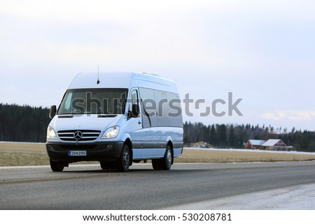 JOKIOINEN, FINLAND - DECEMBER 3, 2016: White Mercedes-Benz Sprinter minibus at speed on the road in winter.