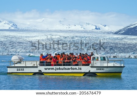 Jokusarlon, Iceland, July 7th 2014. - Tourists wearing life vests ride on amphibian vehicle named 'Dreki' on glacial lake in southeastern part of Iceland. - stock photo