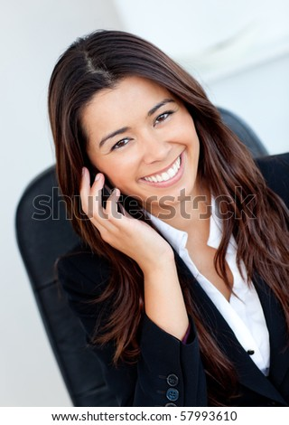Jolly asian businesswoman talking on phone against white background - stock photo