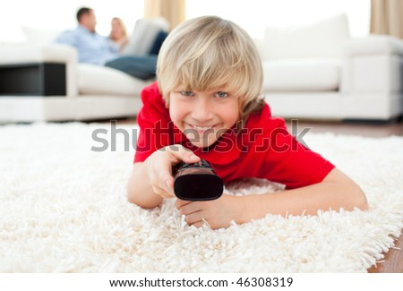 Jolly boy watching TV lying on the floor in the living-room - stock photo