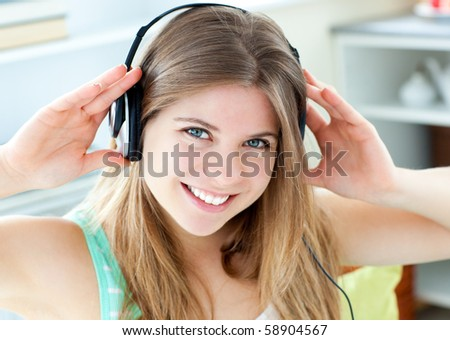 Jolly caucasian woman listen to music with headphones in the kitchen