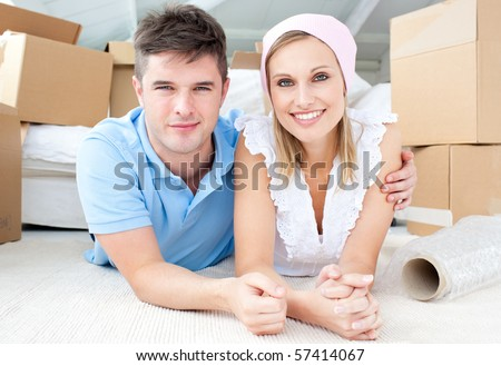 Jolly couple lying between boxes  in their new house - stock photo