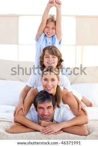 Jolly family having fun in the bedroom - stock photo