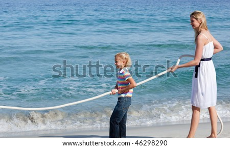 Jolly family playing tug of war at the beach - stock photo