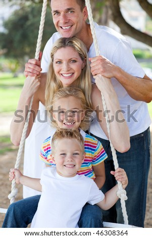 Jolly family swinging in a park - stock photo