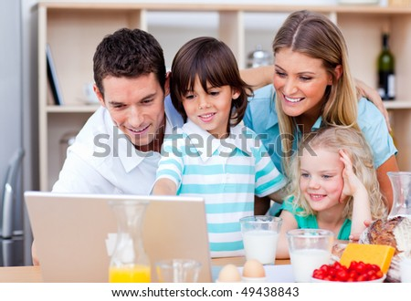 Jolly family using laptop during the breakfast in the kitchen - stock photo