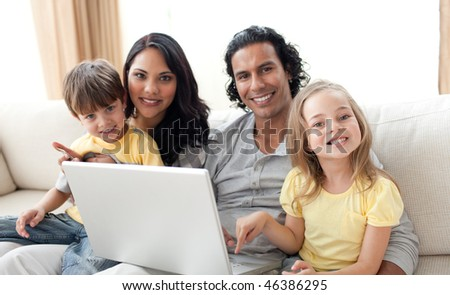 Jolly family using laptop on sofa in the living room