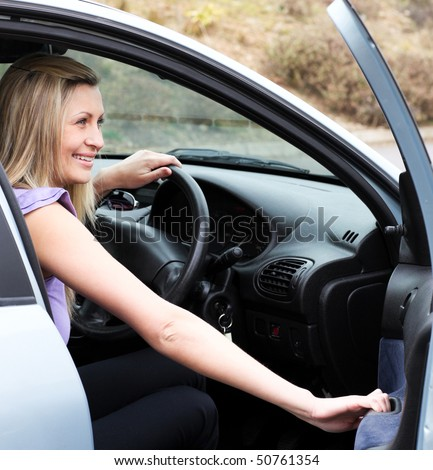 Jolly female driver at the wheel sitting in her car - stock photo