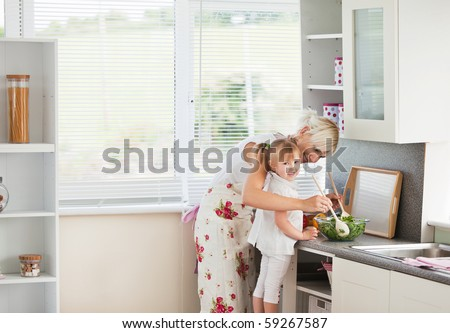 Jolly girl preparing a salad with her mother in the kitchen - stock photo