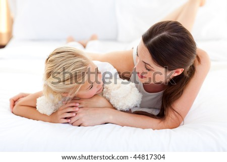 Jolly mother talking with her little girl lying on a bed
