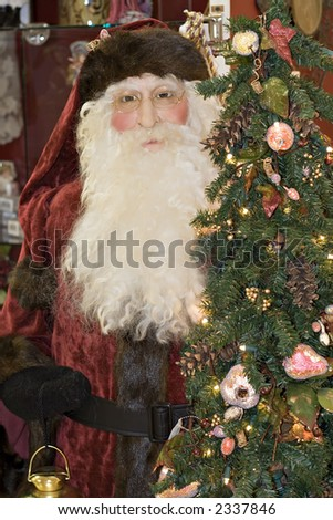 Jolly Old St. Nick (Santa Claus) next to Christmas tree. - stock photo