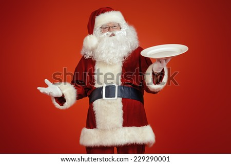 Jolly Santa Claus holds big white plate over festive red background. Copy space. Christmas treats.  - stock photo