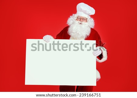Jolly Santa Claus in a chef's hat over festive red background. Copy space. Christmas treats.  - stock photo