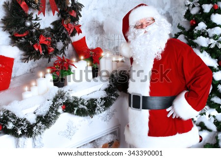 Jolly Santa Claus standing by the fireplace in a room, decorated for Christmas. - stock photo