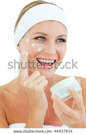 Jolly woman putting cosmetic cream on her face