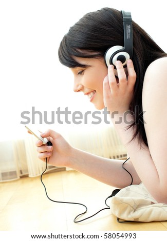 Jolly young woman listen to music lying on the floor in the living room - stock photo