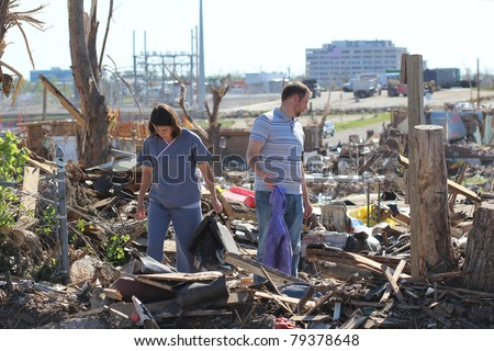 JOPLIN, MO - JUNE 15: A young couple hunts through what's left of their home three weeks after an EF-5 tornado destroyed it on June 15, 2011 in Joplin, MO.  Cleanup is underway but will take time. - stock photo