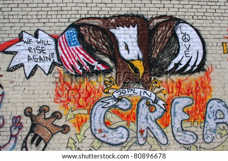 JOPLIN, MO, USA--JULY 12:  Graffiti on the walls of damaged buildings in Joplin, MO where an EF-5 tornado passed through the town on May 22, 2011. - stock photo