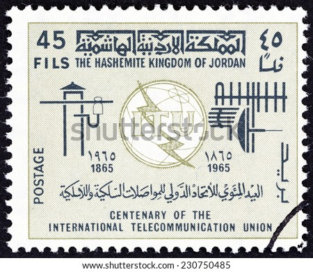 JORDAN - CIRCA 1965: A stamp printed in Jordan issued for the 100th anniversary of I.T.U. shows emblem and symbols, circa 1965.  - stock photo
