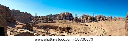 Jordan Petra desert panorama with a toms in the distance and blue sky above. Temple and tombs visible - stock photo