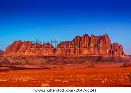 Jordanian Desert Mountain in Wadi Rum, Jordan at twilight. Wadi Rum is known as The Valley of the Moon and a UNESCO World Heritage Site. - stock photo