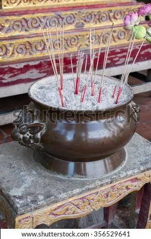 joss stick in joss stick pot on white background; incense in incense burner - stock photo