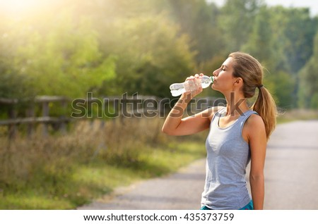 Joung woman drink water while jogging outdoors