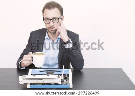 Journalist having his first morning coffee in the office - stock photo