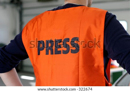 Journalist wearing press safety vest.