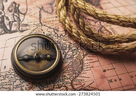 Journey. Compass and rope on a map - stock photo