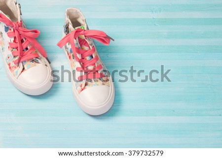 Journey travel concept.Child's female kid's textile sneakers shoes on blue wooden background empty space for text. - stock photo