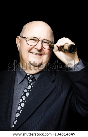 Jovial elderly businessman acting with forethought and intelligence looks through a telescope searching for future business opportunities and strategies - stock photo