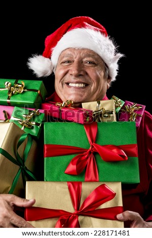 Jovial male senior with broad grin is peering across a load of presents that he is carrying against his chest. Gifts wrapped in plain red, green, magenta and gold. Red Father Christmas cap and coat. - stock photo