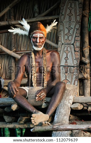 JOW VILLAGE, ASMAT PROVINCE, NEW GUINEA, INDONESIA - JUNE 28: Asmat with a traditional painting on a face, in a cap from cassowary feathers. June 28, 2012 in Jow Village, Asmat province, Indonesia - stock photo