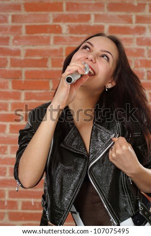 Joy Caucasian woman with a microphone singing against a brick wall - stock photo