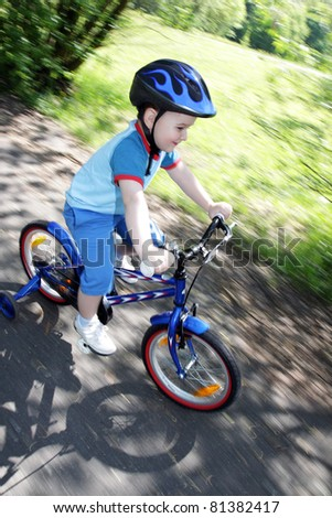 joy game on child bicycle in spring in park - panning shot - stock photo