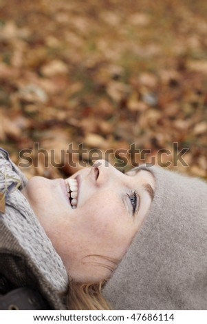 Joy of Autumn - Cute woman Lying in leaves - stock photo