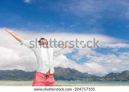 joy of life and freedom expressed by a young man on the beach, standing with hands in the air - stock photo