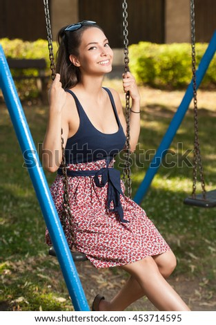 Joy of life, gorgeous young brunette woman having fun on a swing.