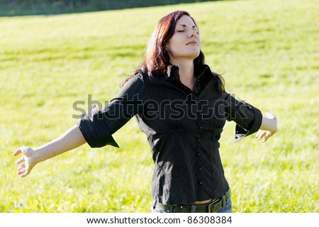 Joy of life, woman with outstretched arms. Sunny outdoor shot. - stock photo