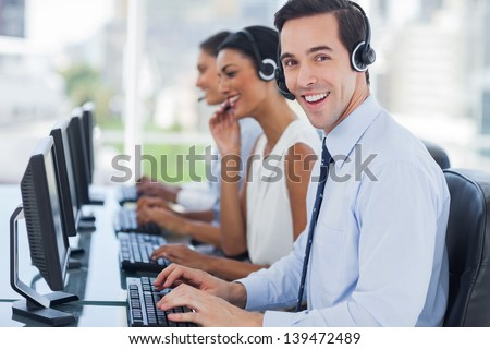 Joyful agent working in a call centre with his headset - stock photo