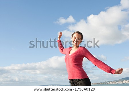 Joyful and attractive young woman feeling happy and raising her arms up to the intense blue sky in celebration. Fun and energetic expression on a colorful spacious sunny sky.