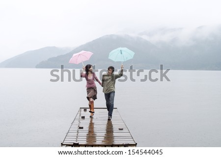 Joyful and spontaneous japanese couple in love, holding hands and running on a wooden pier on a natural lake and mountains landscape, having fun and laughing outdoors. - stock photo