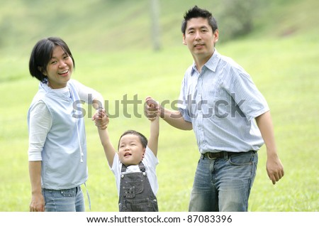 Joyful Asian family together in the park