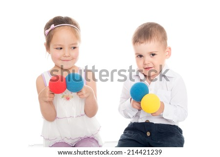 Joyful Asian girl and European boy playing with balls.