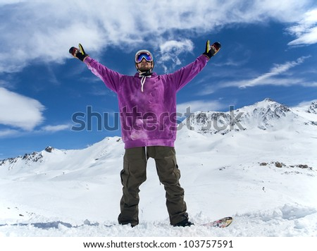 Joyful athlete snowboarder on the background beautiful mountains and blue sky with clouds - stock photo